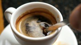 与蓬松泡沫的黑热的浓咖啡咖啡与在一个加奶咖啡杯子的金属茶匙混合 股票视频