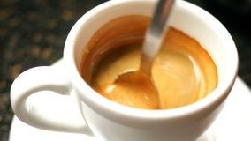 与蓬松泡沫的黑热的浓咖啡咖啡与在一个加奶咖啡杯子的金属茶匙混合 股票录像