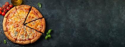 与蓬蒿、蕃茄和橄榄油的可口意大利比萨四乳酪在一张黑暗的具体桌上 与拷贝空间的顶视图 平面 库存照片