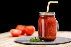 与蓬蒿叶子和秸杆的新鲜的蕃茄圆滑的人在桌面 免版税库存照片