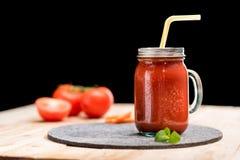 与蓬蒿叶子和秸杆的新鲜的蕃茄圆滑的人在桌面 免版税库存图片