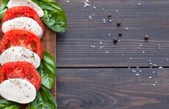 与蓬蒿叶子的蕃茄和无盐干酪切片 免版税库存照片