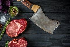 与蓬蒿的新鲜的未加工的牛肉和迷迭香小树枝与轴的在黑木背景的肉的 顶视图 免版税图库摄影