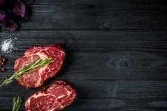 与蓬蒿的新鲜的未加工的牛肉和迷迭香小树枝在黑木背景的 免版税库存图片
