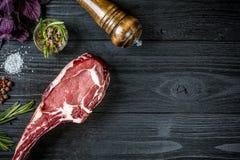 与蓬蒿的新鲜的未加工的牛肉和迷迭香小树枝在黑木背景的 免版税图库摄影