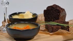 与蓬蒿的新鲜的红色在面包的鱼子酱和黄油在演播室 养殖用与酒杯的红色鱼子酱在背景 冷 免版税库存图片