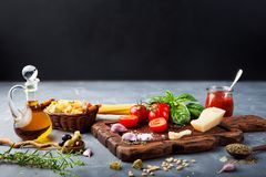 与蓬蒿,意粉,巴马干酪,橄榄油,在石桌上的大蒜成份的意大利食物背景 复制空间 免版税库存图片