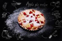 与蔓越桔和图画食谱的苹果饼在黑桌上 免版税库存照片