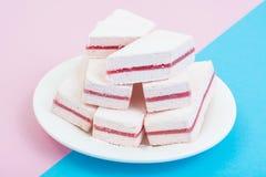 与蔓越桔层数的白色蛋白软糖在淡色背景 库存图片