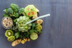 与蔬菜、水果和燕麦粥的新鲜的绿色圆滑的人在一张黑木桌上的一个玻璃杯子 免版税库存照片