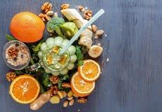 与蔬菜、水果和燕麦粥的新鲜的绿色圆滑的人在一张黑木桌上的一个玻璃杯子 库存照片