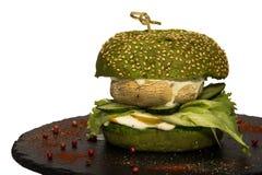 与蔬菜沙拉、蘑菇、黄瓜和调味汁叶子的素食汉堡  免版税图库摄影