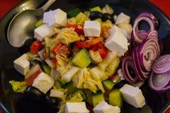 与蕃茄、烤和被剥皮的甜椒和希腊白软干酪混合叶子沙拉穿戴与橄榄油、大蒜和柠檬汁 免版税图库摄影
