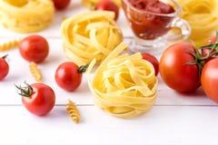 与蕃茄乳酪未加工的面团Fusili意大利细面条成份意大利食物白色背景关闭的面团产品拷贝空间 库存照片