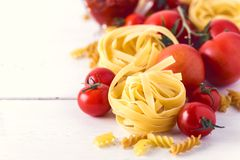 与蕃茄乳酪未加工的面团Fusili意大利细面条成份意大利食物白色背景关闭的面团产品被定调子的拷贝空间 免版税库存照片