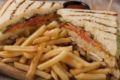 与蕃茄火腿乳酪鸡的烤在一个委员会的三明治和炸薯条用调味汁 图库摄影