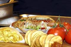 与蕃茄辣调味汁和葱的热狗在木板,水平 免版税库存照片