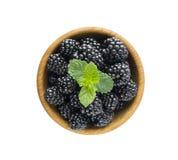 与薄荷的叶子的黑莓在一个木碗 免版税库存照片