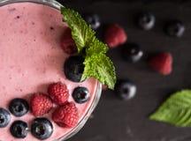 与薄荷的顶视图莓果鸡尾酒superfood饮食奶昔的莓和蓝莓圆滑的人 库存照片