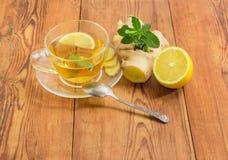与薄菏、姜和柠檬切片的茶在玻璃杯子 免版税库存图片