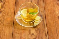 与薄菏、姜和柠檬切片的茶在玻璃杯子 免版税图库摄影