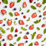 与薄菏的绿色瓣的开胃莓果在灰色背景的 食物布局 平的位置 免版税图库摄影