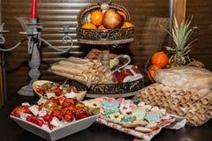 与薄酥饼卷、姜饼曲奇饼和f的充分的圣诞节桌 库存图片
