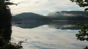 与薄雾上升的湖边小山 图库摄影