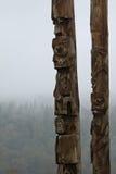 与薄雾的传统Gitxsan图腾柱盖了森林后边 免版税库存照片