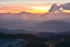 与薄雾的日落山 库存照片