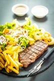 与薯条洋葱圈的烤牛肉肉牛排用调味汁和新鲜蔬菜 免版税图库摄影