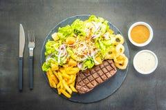 与薯条洋葱圈的烤牛肉肉牛排用调味汁和新鲜蔬菜 免版税库存图片