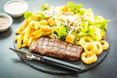 与薯条洋葱圈的烤牛肉肉牛排用调味汁和新鲜蔬菜 库存照片