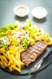 与薯条洋葱圈的烤牛肉肉牛排用调味汁和新鲜蔬菜 库存图片