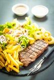 与薯条洋葱圈的烤牛肉肉牛排用调味汁和新鲜蔬菜 免版税库存照片