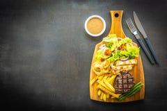 与薯条的烤牛肉肉牛排调味和新鲜蔬菜 库存照片