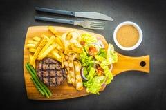与薯条的烤牛肉肉牛排调味和新鲜蔬菜 库存图片
