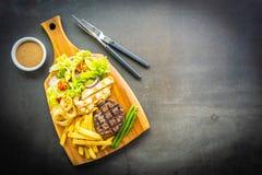 与薯条的烤牛肉肉牛排调味和新鲜蔬菜 免版税库存图片
