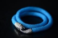 与蛇头锁的蓝色串珠的项链在黑暗的背景 免版税库存图片