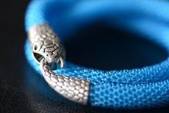 与蛇头锁的蓝色串珠的项链在黑暗的背景 免版税图库摄影