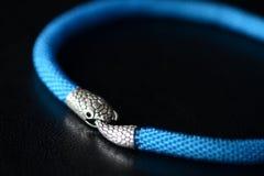 与蛇头锁的蓝色串珠的项链在黑暗的背景 库存图片