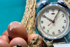与蛋壳和鸡蛋,老打破的闹钟,水稻种子,五颜六色的背景的静物画 库存图片