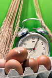 与蛋壳和鸡蛋,老打破的闹钟,水稻种子,绿色背景的静物画 免版税库存图片