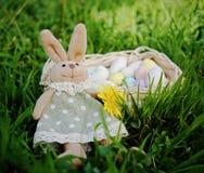与蛋形甜点的篮子在绿草 免版税库存图片