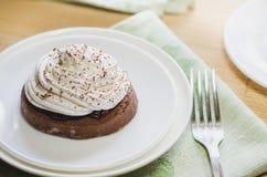 与蛋白奶油的一个巧克力蛋糕在一把白色板材和叉子,位于一面绿色餐巾 免版税库存图片