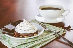 与蛋白奶油的一个巧克力蛋糕,片断,茴香、豆蔻果实和一个杯子在一张木桌上的热的咖啡 图库摄影