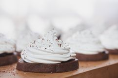 与蛋白奶油的巧克力蛋糕在木板 免版税图库摄影