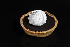 与蛋白甜饼果子馅饼的巧克力蛋糕在一黑背景isola 库存图片