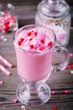 与蛋白软糖和糖心脏的桃红色热巧克力在一个玻璃杯子为情人节 免版税库存图片