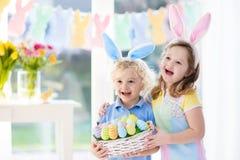 与蛋篮子的孩子在复活节彩蛋寻找 免版税库存照片